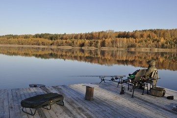 Man fishing for carp from dock over lake near autumn forest
