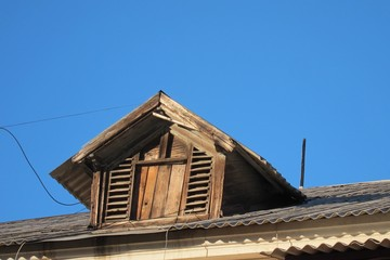 Window on the old roof of the attic against blue sky