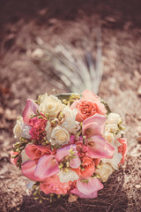 Bridal autumn bouquet with red and white roses over yellow autumn grass.