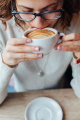 Closeup of woman enjoying in coffee aroma