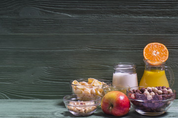 Ingredients for a healthy breakfast: orange juice, yogurt, corn flakes, nuts, honey, tangerines and apples. The concept of a healthy diet, horizontal.