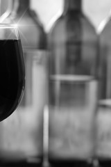 part of the glass with red wine on the background of bottles. the concept of a bar, alcohol. Copy space. Free space for text. black and white photo