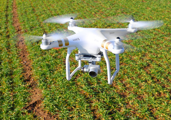 Drone quadrocopter with camera. New tool for farmers use drones to inspect of cultivated fields. Modern technology in agriculture.