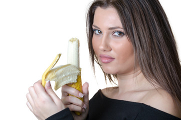 Cute brunette lady wear black shirt, holding and peel a banana standing in profile
