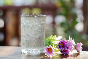 glass of water and fake flower on wood table