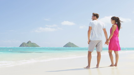 Wall Mural - Beach couple looking at ocean view from behind. Couple standing on white sand in pink dress and beachwear on vacations on Lanikai beach, Oahu, Hawaii, USA with Na Mokulua Islands. SLOW MOTION.