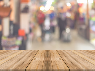 Wooden board empty table in front of people shopping at market fair background. Perspective wood and blur market - can be used for display or montage your products - vintage effect style pictures.