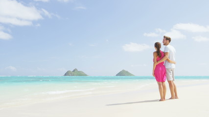 Wall Mural - Beach couple looking at ocean view on Hawaii. Happy couple standing on white sand in pink dress and beachwear on vacations on Lanikai beach, Oahu, Hawaii, USA with Na Mokulua Islands. RED EPIC.