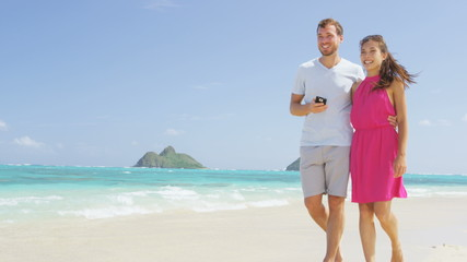 Aufkleber - Phone app - Couple on beach using smartphone. Romantic couple in love on honeymoon having fun on outside on beach holding smartphone walking and laughing. RED EPIC SLOW MOTION.
