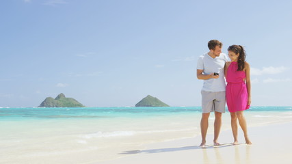 Aufkleber - Couple on beach vacation using smart phone app. Romantic couple in love on honeymoon having fun on Lanikai beach, Oahu, Hawaii. Couple holding smartphone. RED EPIC SLOW MOTION.