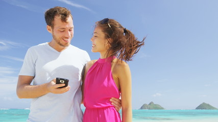 Aufkleber - Beach couple on vacation taking smart phone selfie photograph using smartphone camera. Romantic couple in love on honeymoon on Lanikai beach, Oahu, Hawaii, USA with Mokulua Islands. RED EPIC SLOWMO.