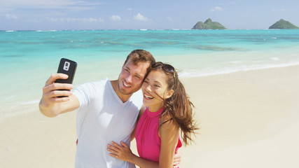 Aufkleber - Couple on beach vacation taking selfie photograph using smart phone. Romantic couple in love on honeymoon on Lanikai beach, Oahu, Hawaii, USA with Mokulua Islands. Couple holding smartphone camera.