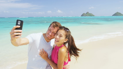 Aufkleber - Smart phone - beach vacation couple taking selfie photograph using smartphone having fun holding smart phone camera on Lanikai beach, Oahu Hawaii, USA. Young Asian Caucasian couple. Shot on RED EPIC.