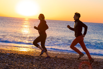 Silhouettes of Man and Woman jogging along Sea Beach at Sunrise