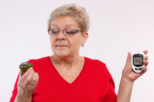 Surprised senior woman holding glucometer and fresh cupcake, measuring and checking sugar level, concept of diabetes