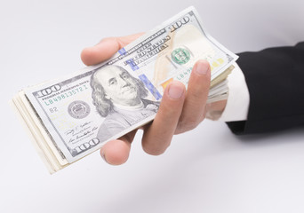 US dollars in business hand isolated on a white background