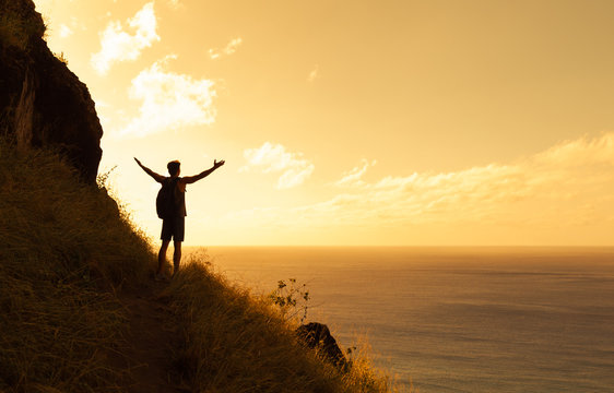 Happy man on top a mountain reaching his army out toward the horizon. Healthy lifestyle and life achievement concept.