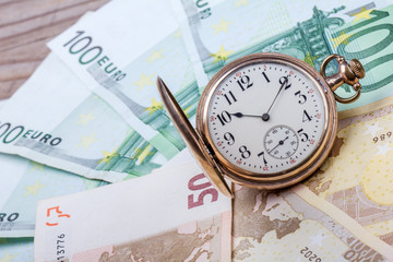 Time is money concept with euros and golden pocket watch.