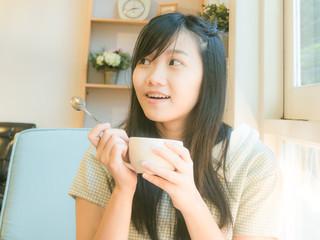 Asian beautiful young woman drinking coffee near window