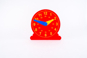 Isolated red plastic clock with for learning time.