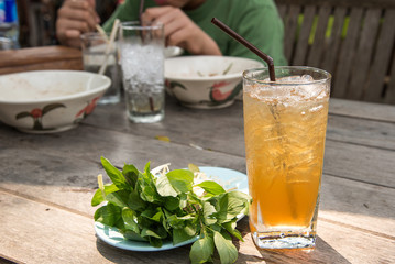 Glass tamarind juice with ice on wooden table