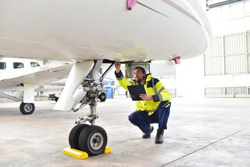 Mechaniker kontrolliert Fahrwerk eines Flugzeuges im Hangar //  Mechanics controlled chassis of an airplane in the hangar
