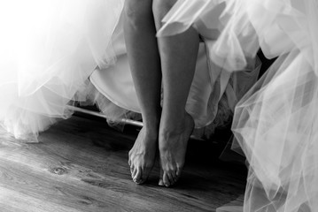 Closeup shot of beautiful bride's legs in white dress b&w