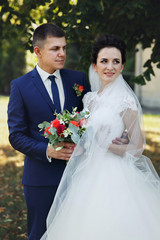 Happy couple of newlyweds, bride and groom posing & hugging in p
