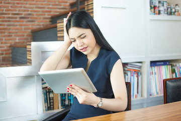 Asian Woman Using Tablet and Thinking with Serious Look