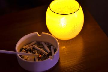 Cigarette in ashtray in dark
