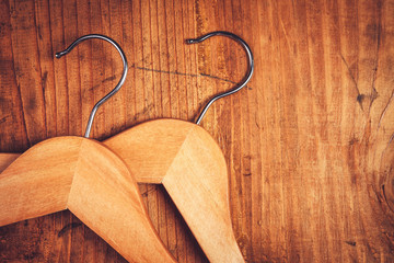 Two retro cloth hangers on rustic wooden background, top view