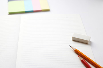 Blank notebook with pencil, red pencil, tag papers,  and eraser on white background.