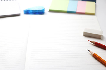 Blank notebook with pencil, red pencil,  tag papers, notepad, correction tape, and eraser on white background.