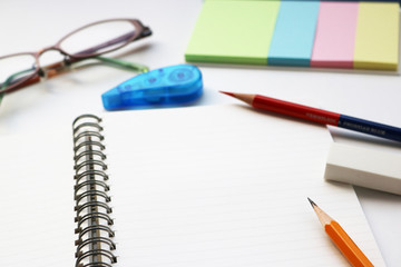 Blank notebook with pencil, red pencil, tag papers, notepad, correction tape, glasses, and eraser on white background.