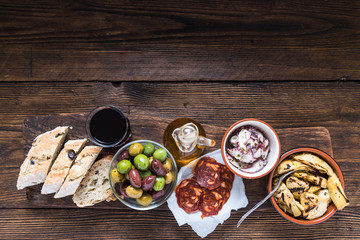 Wooden board with tapas, olives and salami and olive oil