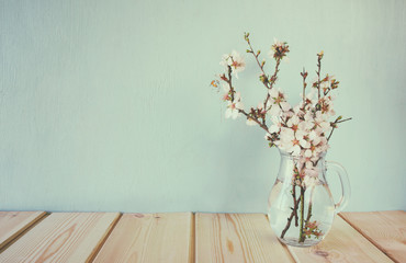 spring bouquet of flowers on the wooden table with mint background. vintage filtered and toned