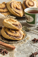 Rolls puff pastry with cinnamon and sugar, tea Cup