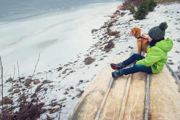 Boy with dog sitting together near frozen lake