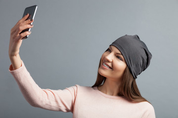 Cheerful girl is photographing herself on telephone