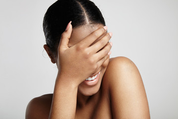 smiling shy woman closed her face with a hand on a white backgro