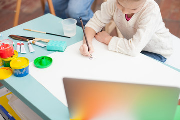 Cheerful female child is painting with grandfather