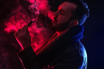 stylish dressed bearded man smoking electronic cigarette in studio