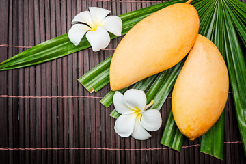 yellow thai mango  with plumeria flower on bamboo background