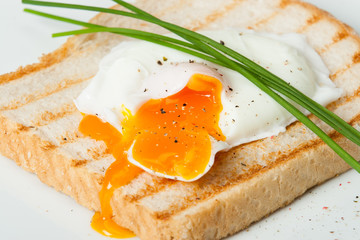 Poached Egg On Toast With Chives And Spices. White Plate