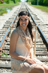 Beautiful senior girl sitting on train tracks.