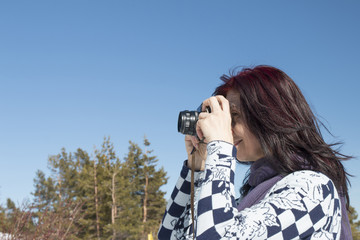 Redhead woman with an old camera