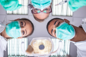 Dental team working with a patient in protective work wear