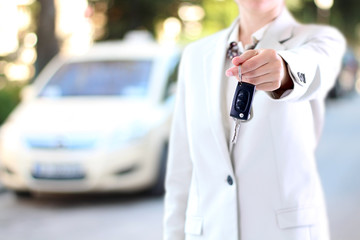 Young successful businesswoman offering a car key.
