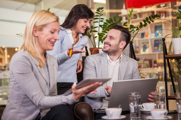 Business partners talking and working in coffee bar