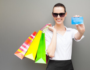 Happy woman holding out credit card and holding shopping bags.